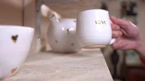 Lycklig flicka som sätter en ren vit kopp som betitlas med guld- text för ` för bokstavs`-FÖRÄLSKELSE på hyllan stock video