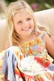 Lycklig flicka som sitter på sofaen arkivbild
