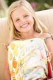 Lycklig flicka som sitter på sofaen arkivfoton