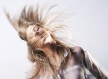 Lycklig flicka som skakar långt blont hår royaltyfri bild