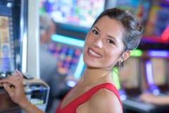 Lycklig flicka som spelar enarmade banditer i Las Vegas royaltyfri foto