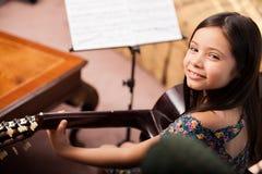 Lycklig flicka som spelar gitarren arkivbild