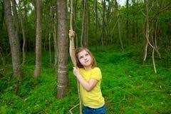 Lycklig flicka som spelar i den Forest Park djungeln med lianen Arkivbild