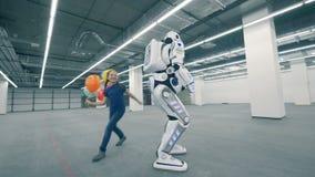 Lycklig flicka som spelar med en robot, slut upp stock video