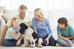 Lycklig flicka som spelar med hunden medan familj som ser henne royaltyfri bild