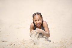Lycklig flicka som spelar på stranden i sanden arkivbild