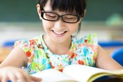 Lycklig flicka som studerar i klassrumet royaltyfria bilder