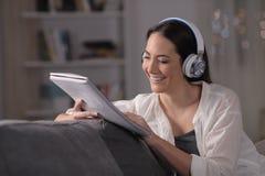Lycklig flicka som studerar lyssnande online-kurs för läsninganmärkningar fotografering för bildbyråer