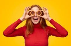 Lycklig flicka som täcker ögon med kakor arkivfoto