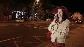 Lycklig flicka som talar på mobiltelefonen i nattstad stock video