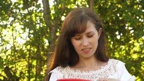 Lycklig flicka som ?ter jordgubbar i sommar i tr?dg?rden l?cker efterr?ttjordgubbe den h?rliga flickan ?ter den r?da jordgubben lager videofilmer