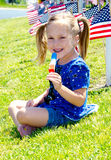 Lycklig flicka som tycker om en isglass på 4th Juli Royaltyfri Foto