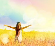 Lycklig flicka som tycker om lyckan på solig äng Arkivbild