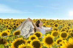 Lycklig flicka utomhus i vårsolrosfält Royaltyfria Foton