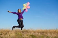 Lycklig flickabanhoppning med ballonger. Arkivfoton