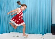 Lycklig flickabanhoppning på sängen royaltyfria foton