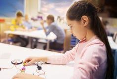Lycklig flickabyggnadsrobot på robotteknikskolan royaltyfri fotografi