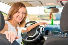 Lycklig flickachaufför bak hjulet av bilen Royaltyfri Bild