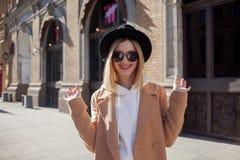 Lycklig flickadet fria, solig dag Trendig och moderiktig ung kvinna i svart klädd med filt hatt och stilfullt beige lag arkivfoto