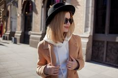 Lycklig flickadet fria, solig dag Trendig och moderiktig ung kvinna i svart klädd med filt hatt och stilfullt beige lag fotografering för bildbyråer