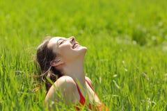 Lycklig flickaframsida som andas ny luft i en äng Royaltyfri Foto
