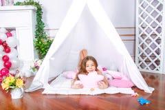Lycklig flickalek hemma Roligt barn som har gyckel i barnrum royaltyfri bild