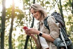 Lycklig flickamessaging på mobiltelefonen under resa arkivbild