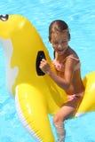 Lycklig flickasimning på barnens uppblåsbara leksak Royaltyfri Fotografi