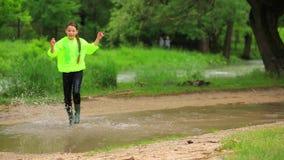 Lycklig flickaspring i stor pöl i parkera stock video