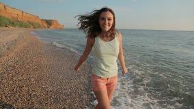 Lycklig flickaspring längs stranden barfota och stock video