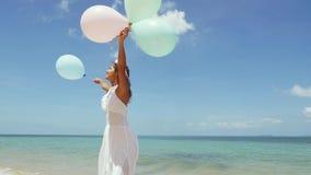 Lycklig flickaspring på stranden som rymmer sväller i händer som omkring rotera långsam rörelse Begreppslycka, frihet stock video