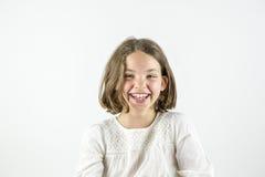 Lycklig flickastående som isoleras på vit arkivbild
