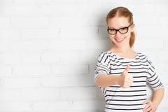 Lycklig flickastudent i exponeringsglas som visar tummen upp från ett bric mellanrum royaltyfria bilder