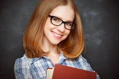 Lycklig flickastudent med exponeringsglas och boken från svart tavla Royaltyfria Foton