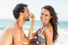 Lycklig flickvän som sätter sunscreen på pojkvännäsa royaltyfri fotografi
