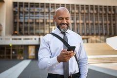 Lycklig formell affärsman som använder telefonen på gatan royaltyfria foton