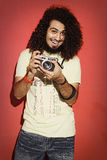 Lycklig fotograf som skrattar med härlig lång holdi för lockigt hår royaltyfri fotografi