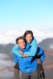 Lycklig fotvandra piggybacking för par Arkivfoto