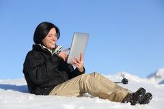 Lycklig fotvandrarekvinna som bläddrar en minnestavla på snön Royaltyfria Bilder