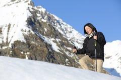 Lycklig fotvandrarekvinna som trekking på det insnöat berget Arkivbild