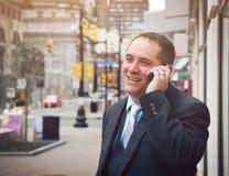 Lycklig frank affärsman som talar på mobiltelefonen arkivbild