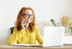 Lycklig Freelancer som i regeringsställning arbetar och att tala på telefonen arkivfoton