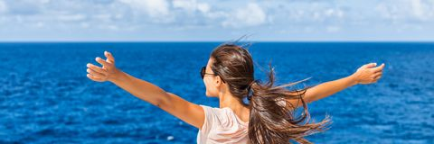Lycklig frihetskvinna med öppna armar som ser havet arkivbilder