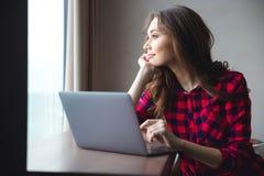 Lycklig fundersam kvinna som använder bärbar datordatoren Royaltyfri Foto