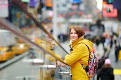 Lycklig fyrkant för sight för ung kvinna turist- tidvis i New York City Kvinnlig handelsresande som tycker om sikt av i stadens c royaltyfria foton