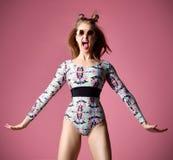 Lycklig gången ut nätt skrika kvinna i roligt hoppa för solglasögon nära den rosa väggen fotografering för bildbyråer