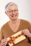 Lycklig gammal dam med gåva Arkivbilder