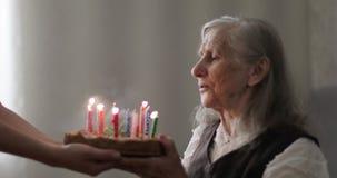Lycklig gammal kvinna med ett grått hår som blåser stearinljus på en kaka arkivfilmer