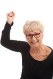 Lycklig gammal kvinna som har stängt nävar. Arkivfoton