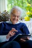 Lycklig gammalare kvinna som använder en tablet och skratta arkivfoton